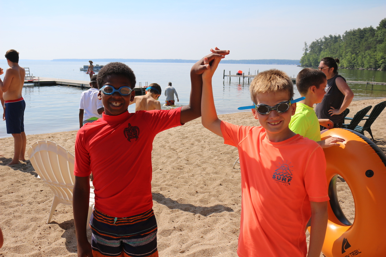 boys high fiving on the lake at summer camp in maine